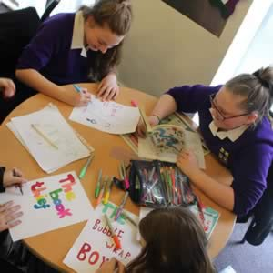 Girls making posters during Book Club enrichment